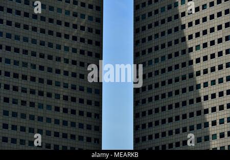 Vorderansicht von zwei modernen High Rise office Towers framing ein blauer Himmel in Singapur als abstrakt Hintergrund mit starken Geometrie und Symmetrie