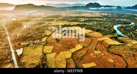Aerial Vogelperspektive sonnenaufgang Blick auf Tal Landschaft mit Heißluft-Ballon, Nebel, Karst in den Bergen, Fluss und die Reisfelder. Laos, Vang Vieng. - Stockfoto