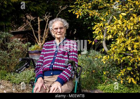 Ältere Frau in ihrem Garten in West Sussex England sitzen - Stockfoto