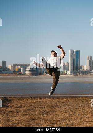 Junge männliche parkour Sportler führt akrobatische Sprünge vor der Skyline - Stockfoto