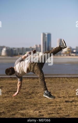 Junger Mann parkour Sportler führt akrobatische Sprünge vor der Skyline - Stockfoto