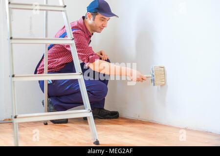 Ansicht von unten ein Maler des Menschen in der Arbeitswelt mit einer Walze, Schaufel und Leiter - Stockfoto