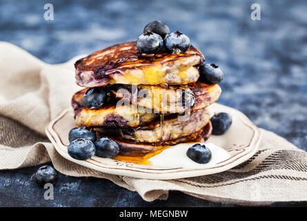Stapel von frisch zubereiteten Blueberry ricotta Pfannkuchen mit frischen Beeren, Joghurt und Honig zum Frühstück - Stockfoto