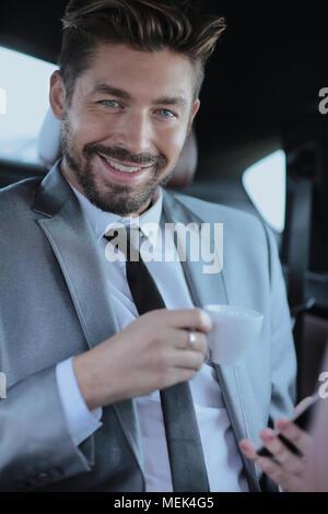 Geschäftsmann Kaffee trinken auf dem Rücksitz eines Autos - Stockfoto