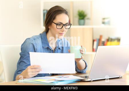 Selbständige, die online arbeiten mit einem Laptop Dokumente zu Hause Vergleich konzentriert - Stockfoto