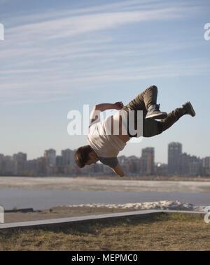 Junger Mann parkour Sportler führt Tricks vor der Skyline - Stockfoto