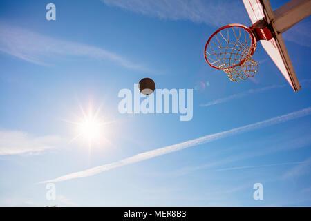 Basketball, Basketball bal in Hoop an einem sonnigen Tag