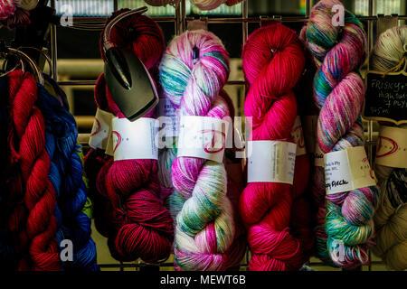 Mehrfarbige Knäuel Wolle beleuchtet durch einen Scheinwerfer auf ein Einzelhändler bei Yarndale, Skipton, North Yorkshire, UK. - Stockfoto