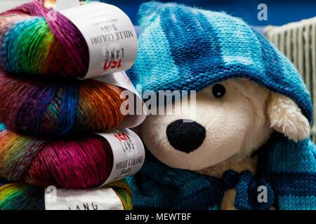 Die Händler stehen mit Strängen von mehrfarbigen Wolle und Spielzeug Hund mit gestrickten Decke an Yarndale, Skipton, North Yorkshire, UK. - Stockfoto