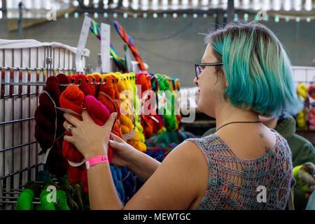 Frau mit türkis gefärbte Haare, griffen die hellen und farbenfrohen Kammgarn Stränge an Yarndale, Skipton, North Yorkshire, UK. - Stockfoto