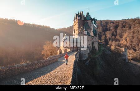 Panorama Ansicht der jungen Person in der roten Jacke auf dem Weg zum berühmten Burg Eltz beleuchtet im schönen Morgen bei Sonnenaufgang mit Lens flare - Stockfoto