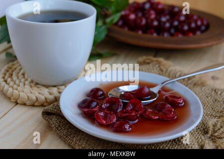Cherry Marmelade und einer Tasse Tee auf einem hellen Hintergrund. Die Ansicht von oben - Stockfoto