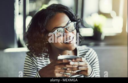 Lächelnden jungen afrikanischen Frau Brille trägt allein sitzen an einem Tisch in einem Café genießen Sie eine frische Tasse Kaffee - Stockfoto