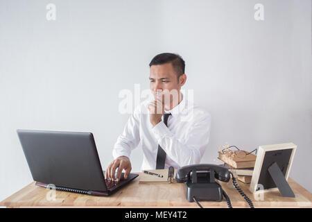 Ein junger Geschäftsmann auf der Suche gedrückt und von der Arbeit in der Sitzung Büro indors besorgt - Stockfoto