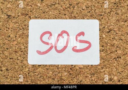Wort SOS handschriftlich auf einem Aufkleber an eine Pinnwand angeheftet - Stockfoto