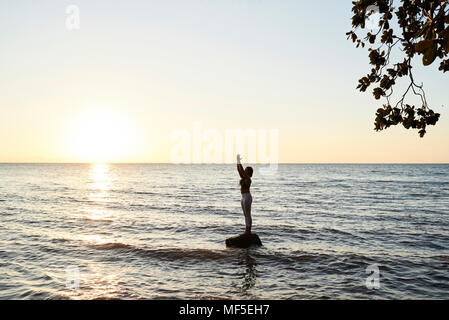 Junge Frau mit Yoga auf einem Felsen im Meer bei Sonnenuntergang - Stockfoto