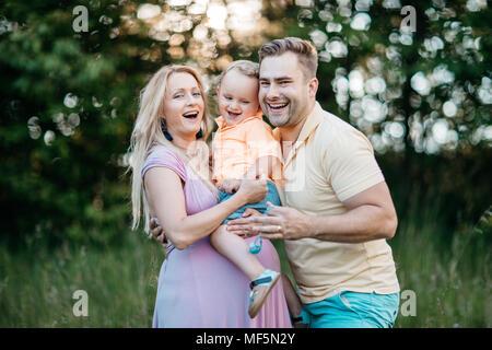 Eine glückliche Familie zusammen Spaß draußen in der Natur. Das Porträt einer schwangeren Frau und ihrem Partner ihren jungen Sohn kuscheln. - Stockfoto