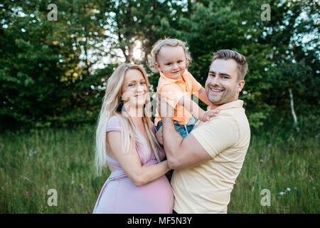 Eine glückliche Familie, die Zeit in der Natur. Das Porträt einer schwangeren Frau und ihrem Partner ihren jungen Sohn umarmen. - Stockfoto