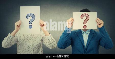 Geschäftsmann und Geschäftsfrau, die ihre Gesichter mit weißem Papier mit Fragezeichen, wie eine Maske, für das Verstecken von Identität. Grau isoliert - Stockfoto