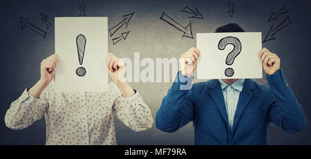 Geschäftsmann und Geschäftsfrau, die ihre Gesichter mit weißem Papier mit gezogenen Verhör und Ausrufezeichen, wie eine Maske, für das Verstecken von id - Stockfoto