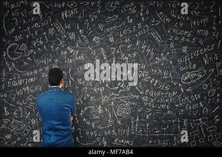 Rückansicht eines verwirrten Geschäftsmann vor einem riesigen Tafel versuchen Mathematik Berechnung, Formeln und Gleichungen zu lösen. Das Denken des Projekts - Stockfoto