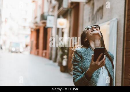 Lachende junge Frau mit guten Nachrichten