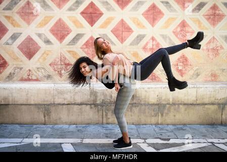 Lachende Frau, die ihren besten Freund Huckepack - Stockfoto