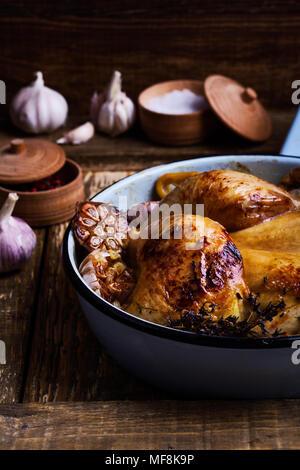 Gebratenes Hähnchen mit Knoblauch, Thymian und Zitrone im Kochen Pfanne auf rustikalen Holzmöbeln Hintergrund - Stockfoto