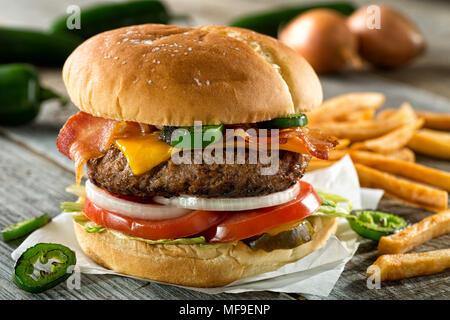 Eine leckere Burger mit Speck, Cheddar, jalapeno Pfeffer, Tomaten, Zwiebeln, Gurken und Salat mit Pommes frites. - Stockfoto