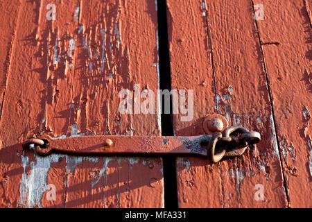 Das Leben eines antiken Red Barn Tür mit abblätternde Farbe und alten schmiedeeisernen Haken - Stockfoto