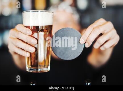 Barkeeper Mann erstreckt sich Glas Bier und beerdeckel. - Stockfoto
