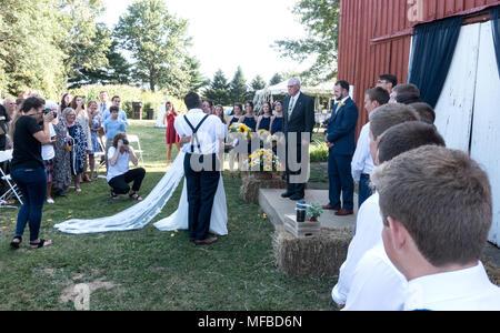 Vater der Braut erhält eine große Umarmung von seiner Tochter, während Minister & Bräutigam warten an der Scheune Kanzel die Zeremonie zu beginnen. Champaign Illinois IL USA - Stockfoto