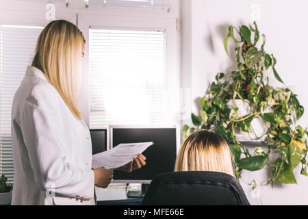 Zwei junge Kolleginnen in Treffen und Diskutieren Schreibarbeit. Manager neue Kandidaten auf der Suche nach Job diskutieren, wählen Sie am besten wieder einladen - Stockfoto