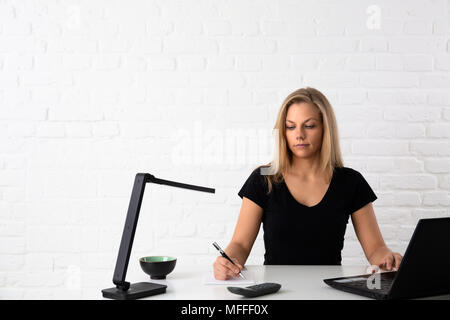 Attraktive junge Frau sitzt mit Notebook im Büro Schreibtisch vor einer Mauer und einige Notizen zu machen - Stockfoto