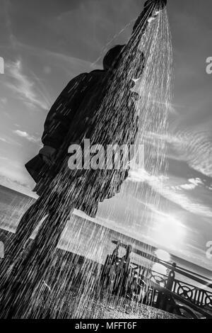 Junge Mädchen steht an der Wand hinter einem Strand Dusche, Hove, Sussex, England, UK, während der sonnigen Englisch winter Abend, während das Wasser spritzt und fällt. - Stockfoto