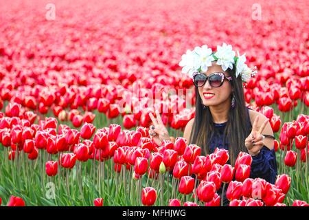 Junge Frau in einem Feld von Tulpen mit Ihren Fingern zeigt, ein Friedensabkommen zu unterzeichnen. Sie trägt ein Blumenstrauß aus weißen Blumen auf dem Kopf und eine Sonnenbrille. - Stockfoto