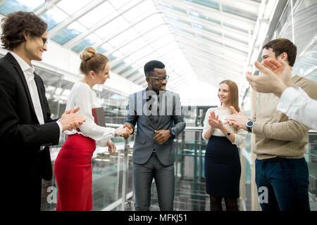 Multirassischen Geschäftsleute die Vereinbarung, ihre Kollegen stehen in der Nähe von - Stockfoto