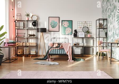 Pastellrosa und smaragdgrünen Dekorationen und Textilien im botanischen Schlafzimmer Innenraum mit skandinavischen Möbeln und Blätter Muster Tapete - Stockfoto