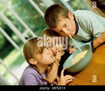 Zwei Mädchen und ein Junge Essen Nudeln am Tisch Ref: CRB 342_10021_048 obligatorische Credit: Peter Müller/Photoshot - Stockfoto
