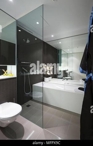 modernes bad mit dusche und badewanne neben einem spiegel und armatur mit waschtisch nachts. Black Bedroom Furniture Sets. Home Design Ideas