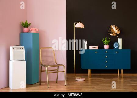 Goldene Stuhl, blaues Gehäuse, Lampe und weißen Verstärker in einem pastellfarbenen Zimmer innen - Stockfoto