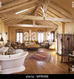 Freistehende Badewanne im offenen Schlafzimmer mit rosa Treppe ...