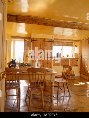 ... Steinplatten Bodenbelag Und Deckenbalken · Kiefer Tisch Und Stühlen In  Der Mitte Des Gelben Küche Im Landhausstil   Stockfoto