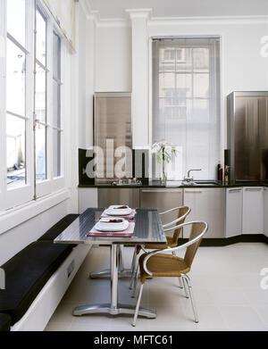 ... Moderne Küche Mit Edelstahl Schränke, Esstisch Mit Sitzbänken,  Fliesenboden, Und Hohen Fenstern.