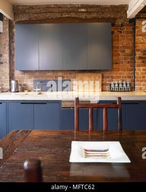 Moderne, Land Küche mit freiliegendem Mauerwerk, blau Vitrinen und einem rustikalen Esstisch aus Holz. - Stockfoto