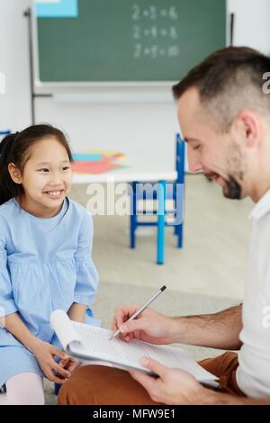 Männliche Lehrer etwas schreiben über die Zwischenablage, während Sie eine privatstunde asiatischen Mädchen neben ihm saß zu fröhlichen - Stockfoto