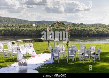 Sonnenuntergang auf dem Fluss. Romantische Hochzeit. Weiße Stühle aus Holz mit Band und Blüten auf einem grünen Rasen. - Stockfoto