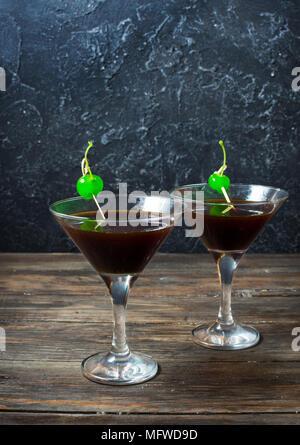 Cocktail schwarze Nacht Tänzer mit Balsam und Cola nach Segmenten einer Zitrone und grün Cherry dekoriert. - Stockfoto