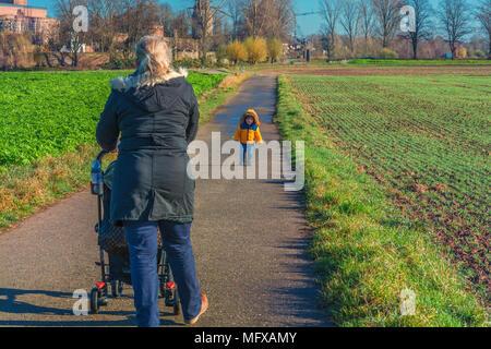 Großmutter mit Enkel beim Wandern und schiebt einen Kinderwagen. - Stockfoto