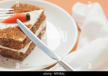 Stück hausgemachten Kuchen mit Karotte Karotte Dekorationen auf weiße Platte close-up, Serviette, Messer, selektiven Fokus - Stockfoto